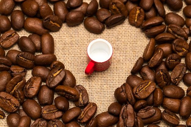Serce z palonych ziaren kawy i filiżanka na tle juty