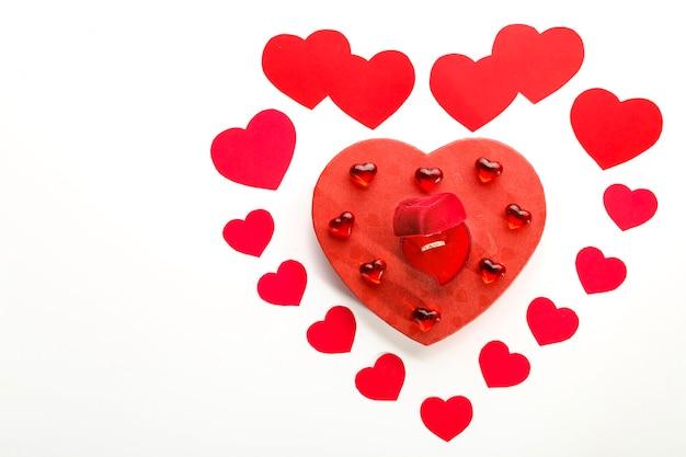 Serce z papierowych serduszek ułożonych na białej powierzchni pośrodku kartonowe serduszko i szklane serduszka oraz pudełko z kółeczkiem
