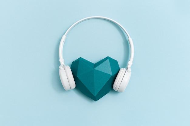 Serce z papieru wolumetrycznego w białych słuchawkach.