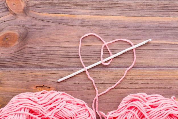 Serce z różowej przędzy, plątaniny nici i igły na drewnianym stole.