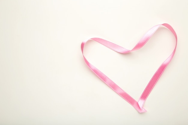Serce z różowej taśmy na białym tle