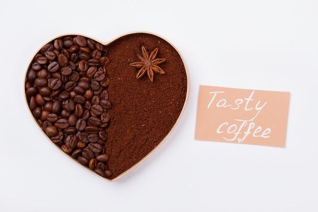 Serce z ziaren kawy i mielonej kawy. miłość do koncepcji smacznej kawy. na białym tle na białej powierzchni