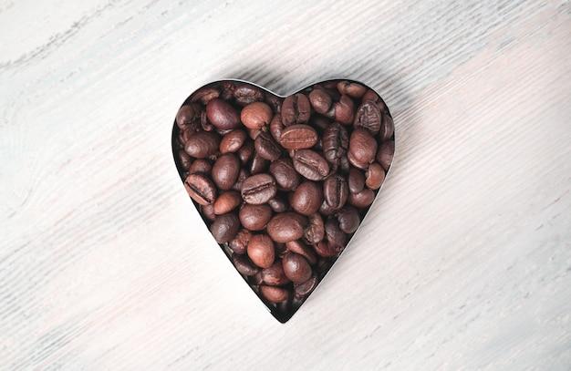 Serce z ziaren kawy na jasnym tle. widok z góry.