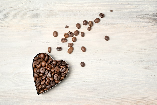 Serce z ziaren kawy w kształcie lecącej komety na jasnym tle. widok z góry z miejscem do skopiowania.
