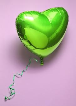 Serce z zielonego balonika na fioletowym tle walentynki