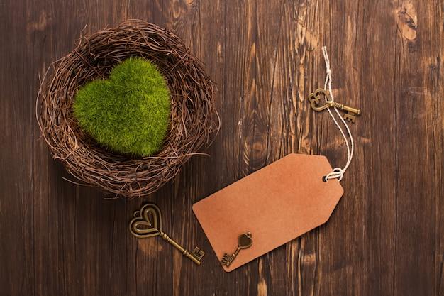 Serce zielony mech w gnieździe, klucze i papierową etykietkę