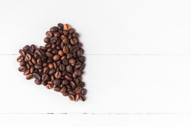 Sercowate ziarna kawy na białym tle drewnianych