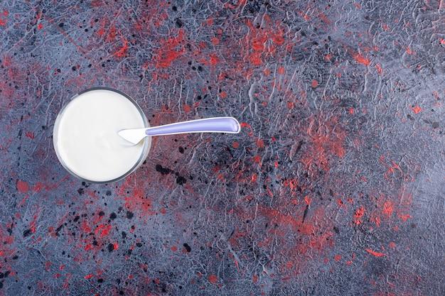 Serek śmietankowy lub jogurt w szklanym kubku.