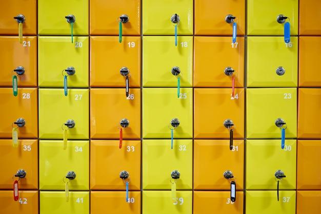 Seria kolorowych, numerowanych szafek z zamkami.