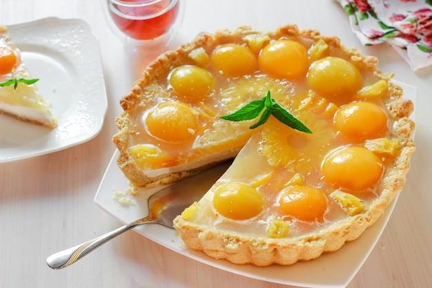 Sernik brzoskwinie z galaretką na białym talerzu