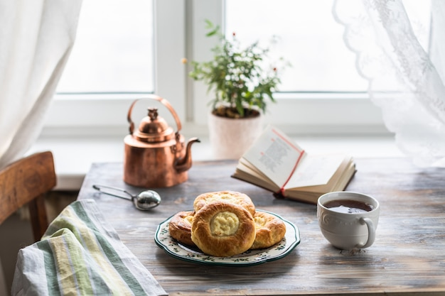 Sernik bułki na śniadanie na drewnianym stole przy oknie z kotem