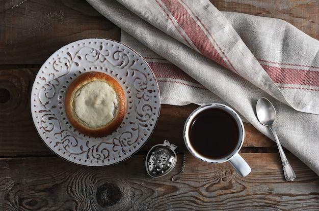Sernik, herbata w kubku na drewnianym rustykalnym