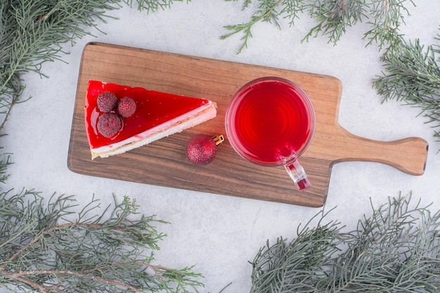 Sernik i szklanka herbaty na desce ze świątecznymi dekoracjami. zdjęcie wysokiej jakości