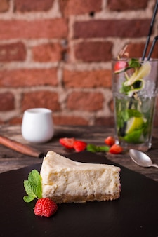 Sernik i truskawka na kamiennym talerzu na nieociosanym drewno stole