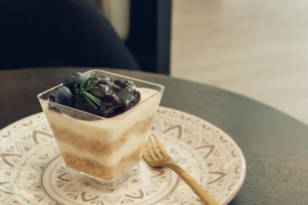 Sernik jagodowy w przezroczystym kubku.