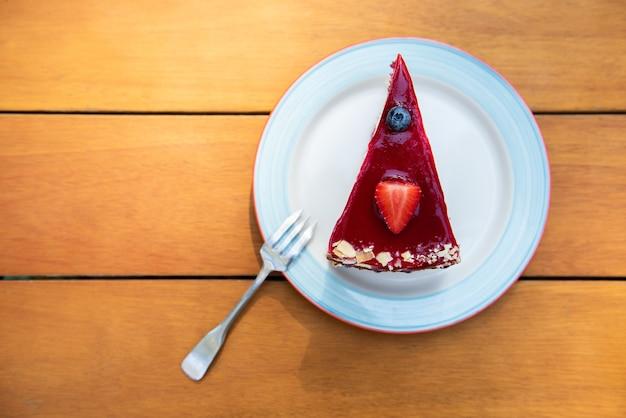 Sernik pokroić w plastry z truskawkami i jagodami