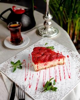 Sernik truskawkowy z truskawkami na wierzchu podany z herbatą
