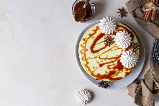 Sernik waniliowy ze skórką z ciasta marchewkowego podany z polewą słonego karmelu i bezą