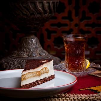 Sernik widok z boku ze szklanką herbaty i cytryny w białej płytce