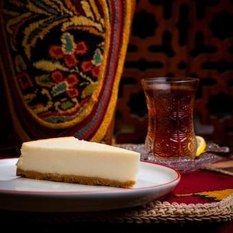 Sernik widok z boku ze szklanką herbaty w białej płytce