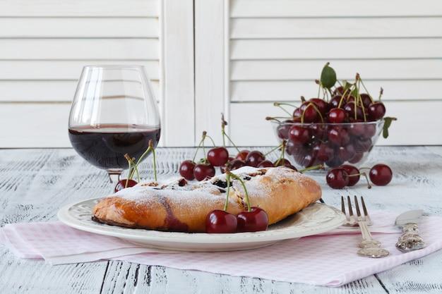 Sernik wiśniowy podawany na talerzu ze słodyczami z czerwonym winem
