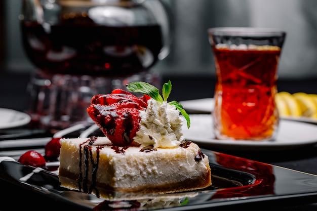 Sernik z boku z syropem czekoladowym, miętą truskawkową bitą śmietaną wiśniową i czarną herbatą