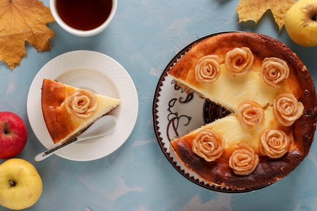 Sernik z jabłkami i filiżanką kawy na jasnoniebieskim tle, ozdobiony różami z jabłek