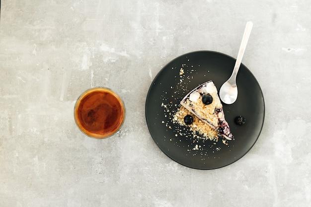 Sernik z jagodami na czarnej płycie w kawiarni.