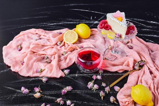 Sernik z owocami i herbatą na różowym płótnie.