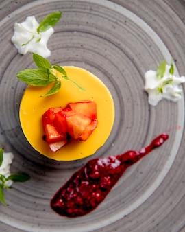 Sernik z owocami na wierzchu podany z sosem jagodowym