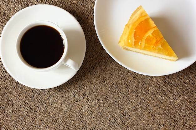 Sernik z pomarańczami na białym talerzu, kubek kawy, spodek na płótnie obrus. widok z góry.