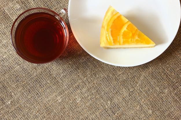 Sernik z pomarańczami na białym talerzu, szklany kubek z herbatą na płótnie obrus. widok z góry.