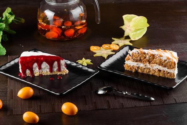 Sernik z sosem jagodowym i ciastem marchewkowym ze śmietaną i karmelem na czarnych kwadratowych talerzach na ciemnym drewnianym stole