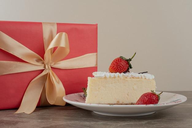 Sernik z truskawkami i prezent na marmurowym stole.