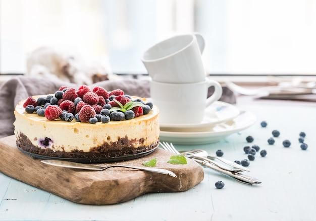 Sernik ze świeżymi malinami i jagodami na drewnianej desce, talerze, kubki, serwetki kuchenne, sztućce na niebieskim tle, okno w tle.