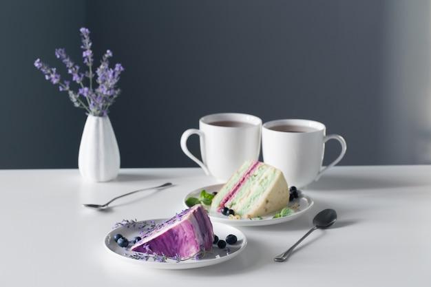 Serniki jagodowe i dwie filiżanki herbaty na białym stole na szarej ścianie w tle