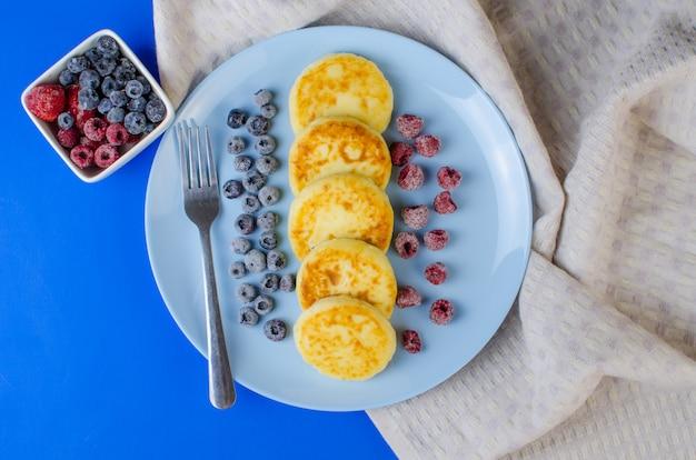Serniki w niebieskim naczyniu z mrożonymi owocami