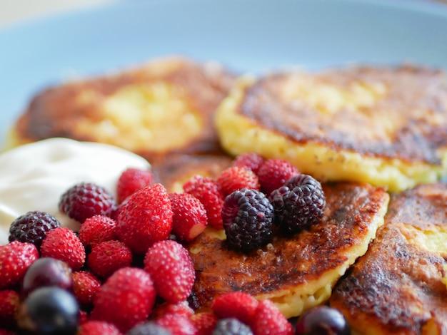 Serniki z jagodami. i kwaśną śmietaną. serniki podawane z dużą ilością świeżych jagód na białym talerzu. wyśmienite śniadanie - twarogowe serniki, twarogowe naleśniki z malinami, truskawkami, blueberrie