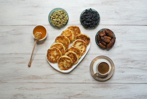 Serniki z miodem, daktylami i kawą na stole.