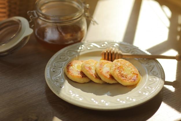 Serniki z miodem i drewnianą łyżką do miodu na talerzu