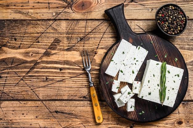 Serową fetę z rozmarynem pokrój na drewnianej desce do krojenia. drewniany stół. widok z góry. skopiuj miejsce.