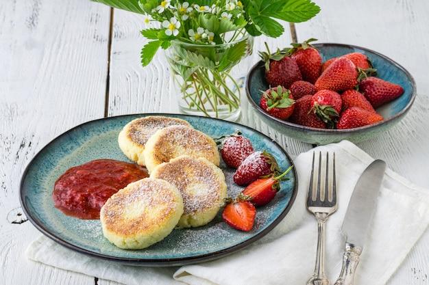Serowe placki, syrniki, twarogi zapiekaj ze świeżymi truskawkami na talerzu
