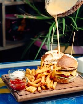 Serowy burger z frytkami na stole