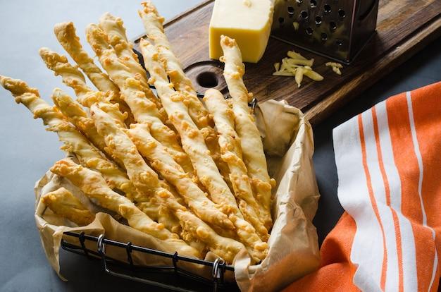 Serowy patyk. paluszki chlebowe z serem na ciemnym tle. koncepcja na przekąskę lub imprezę