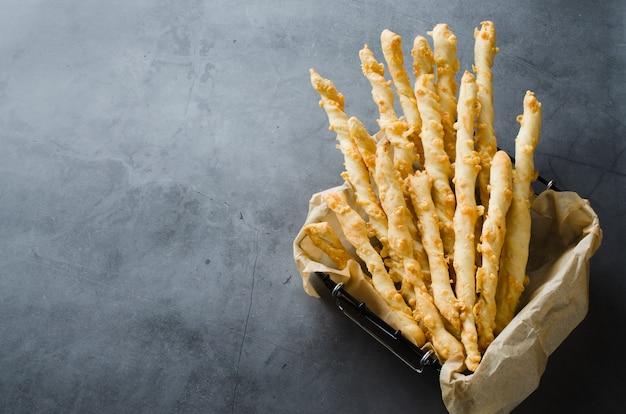 Serowy patyk. paluszki chlebowe z serem na ciemnym tle. pomysł na przekąskę lub imprezę