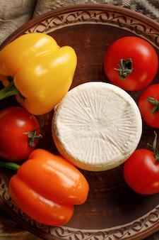 Serowy talerz z pomidorem i papryką na wieśniaku. widok z góry