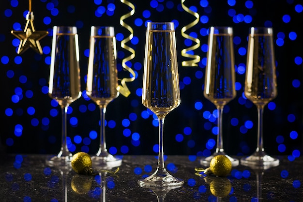 Serpentyna i pięć kieliszków wina musującego na niebieskim bokeh