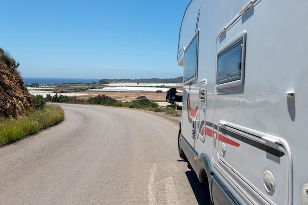 Serpentyna na podrzędnej drodze, na której stoi kamper z widokiem w dal na morze i uprawami w szklarniach