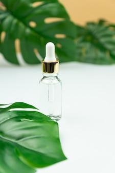 Serum do twarzy w przezroczystej szklanej buteleczce na zielonym liściem i beżowym tle.