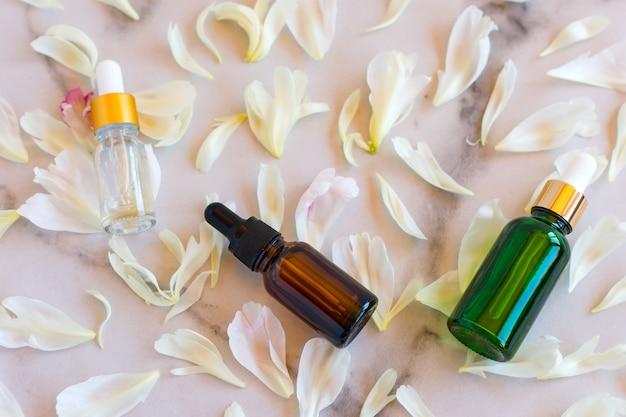 Serum do twarzy w szklanych buteleczkach z pipetą, płatki poeny na marmurowym tle. pusty pakiet etykiet na makiety brandingowe. koncepcja kosmetyków wiosna. naturalny organiczny produkt kosmetyczny.